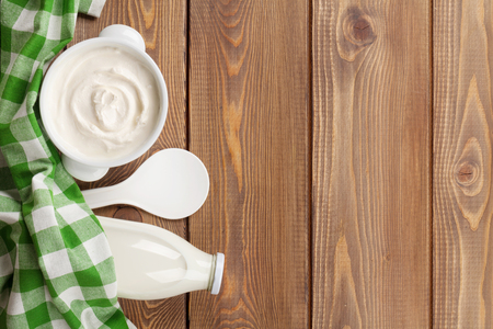 yaourt: Sour cream in a bowl and milk bottle on wooden table. Top view with copy space