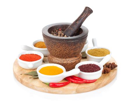 epices: Divers sélection d'épices sur une planche à découper. Isolé sur fond blanc