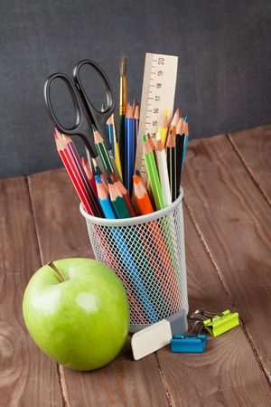 teaching crayons: School and office supplies on classroom table in front of blackboard
