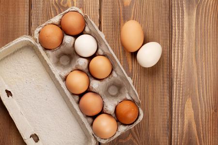 huevo: Caja de cartón de huevo en mesa de madera. Vista superior con espacio de copia