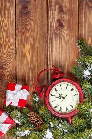 box tree: Christmas wooden background with clock, snow fir tree and gift boxes