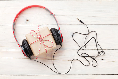 holiday music: Gift box with headphones on wooden table. Top viw