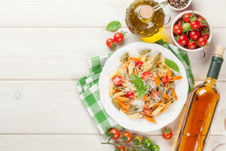 Colorful penne pasta and white wine on wooden table. Top view with copy space