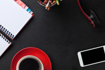 writes: Office leather desk with notepad, coffee cup, smartphone and headphones. Top view with copy space