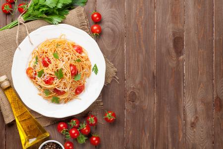 liggande: Spaghetti pasta med tomater och persilja på träbord. Uppifrån med kopia utrymme