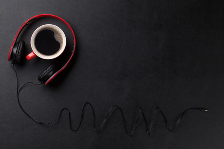 soul food: Headphones and coffee cup on black leather desk table. Music concept. Top view with copy space Stock Photo