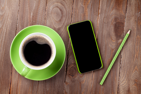 above: Smartphone and green coffee cup on wooden table. Top view