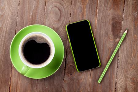 copa: Teléfono inteligente y verde taza de café sobre la mesa de madera. Vista superior Foto de archivo
