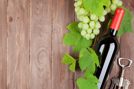 wooden table: Bunch of grapes, red wine bottle and corkscrew on wooden table background with copy space