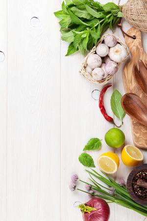 recipe background: Fresh herbs and spices on wooden table. Top view with copy space