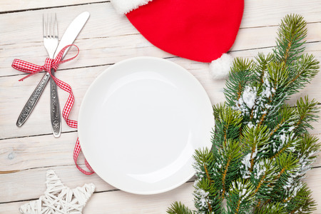 top of the year: Empty plate, silverware and christmas tree. View from above over white wooden table background