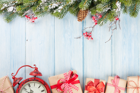 Christmas wooden background with snow fir tree, alarm clock and gift boxes. View with copy space