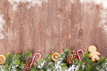 Christmas wooden background with snow fir tree and food decor. View with copy space