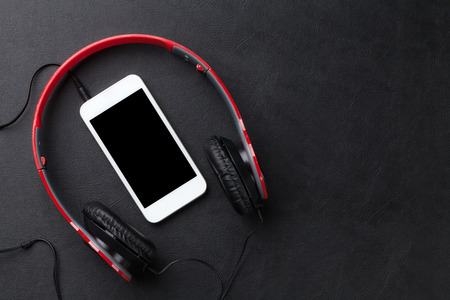 telephone headsets: Headphones and smartphone on black leather desk table. Top view with copy space Stock Photo