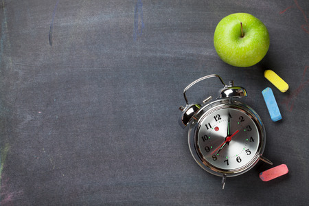 estudiando: Tiza colorido, despertador y manzana en el fondo pizarra. Vista superior con espacio de copia