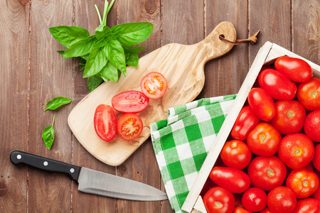 knife tomato: Fresh garden tomatoes cooking on wooden table Stock Photo