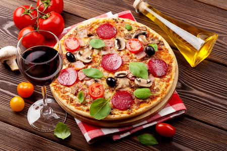 Pizza italiana con peperoni, pomodori, olive, basilico e vino rosso sul tavolo di legno. Vista dall'alto Archivio Fotografico - 45812312