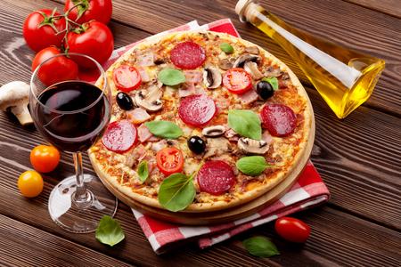 comida italiana: Pizza italiana con pepperoni, tomate, aceitunas, albahaca y vino tinto en la mesa de madera. Vista superior