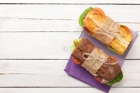 jamon y queso: Dos emparedados con ensalada, jamón, queso y tomates en mesa de madera. Vista superior con espacio de copia