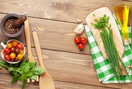 Cooking ingredients on wooden table. Spring onion, basil, tomato, olive oil.