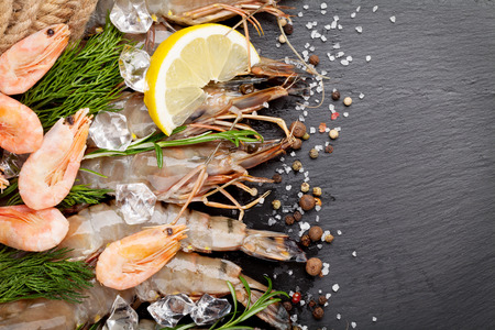 scampi: Fresh prawns with spices on black stone background. Top view with copy space