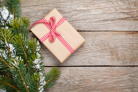 christmas gift box: Christmas fir tree with snow and gift box on rustic wooden board with copy space