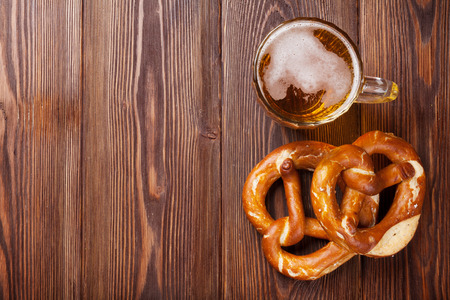 Beer mug and pretzel on wooden table. Top view with copy space