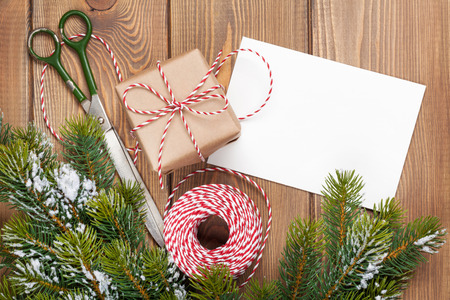 copy space: Christmas presents wrapping and snow fir tree over wooden table background with greeting card copy space