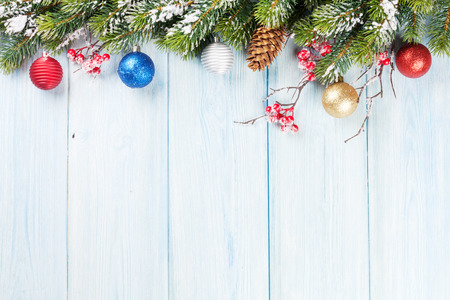 christmas baubles: Christmas wooden background with snow fir tree and decor. View with copy space