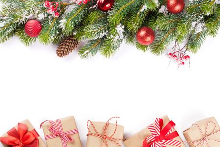 pascuas navideÑas: Rama de un árbol de Navidad con nieve y cajas de regalo. Aislado en fondo blanco con espacio de copia Foto de archivo