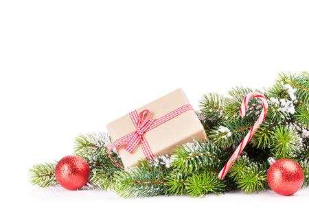 tree  pine: Rama de un �rbol de Navidad con nieve y caja de regalo. Aislado en fondo blanco con espacio de copia