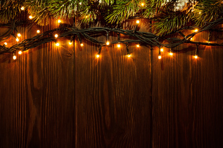 christmas tree ornaments: Christmas tree branch and lights on wooden background. View with copy space Stock Photo