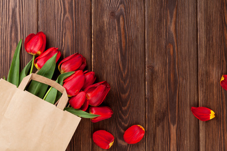 paper bag: Red tulips bouquet in paper bag over wooden table background with copy space