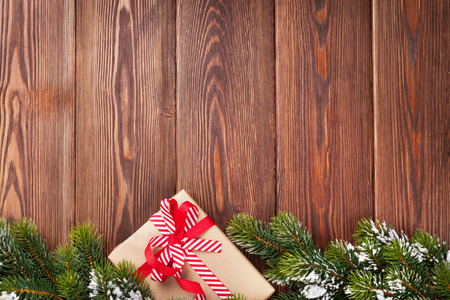 Christmas wooden background with snow fir tree and gift box. View with copy space