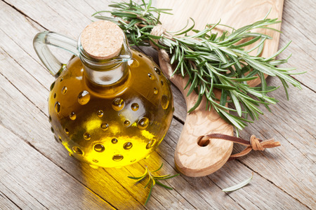 cooking oil: Fresh garden rosemary and olive oil on wooden table
