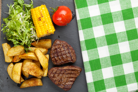 grilled potato: Steak with grilled potato, corn, salad and tomato on stone plate Stock Photo