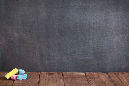 Colorful chalks on classroom table in front of blackboard. View with copy space