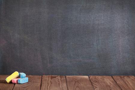 salle de classe: craies color�es sur la table en classe devant tableau noir. Voir avec copie espace Banque d'images