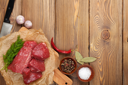 knife tomato: Raw fillet beef steak and spices on wooden table. Top view with copy space Stock Photo