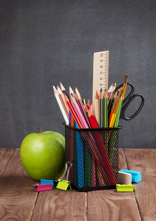 teaching crayons: School and office supplies and apple on classroom table in front of blackboard