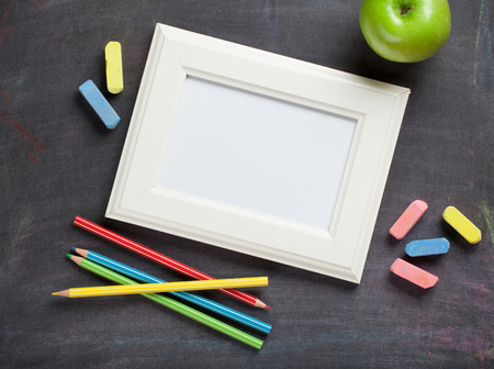 person writing: Photo frame and school supplies on blackboard background. Top view with copy space