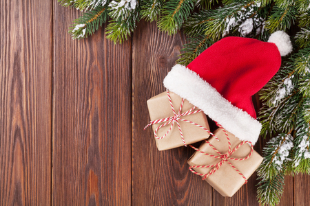 クリスマス ツリー ブランチとサンタ帽子ギフト ボックス木製テーブルの上に。コピー スペース平面図