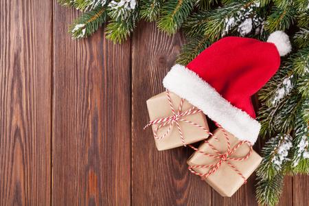 arbol de pino: Rama de un �rbol de Navidad y sombrero de santa con cajas de regalo en la mesa de madera. Vista superior con espacio de copia