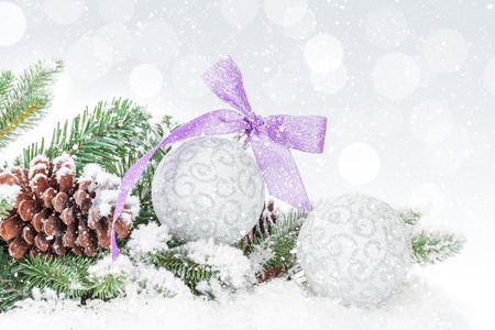 christmas tree purple: Christmas baubles and purple ribbon over snow bokeh background with copy space
