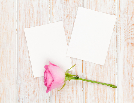 romantic picture: Two blank photo frames and pink rose over wooden table