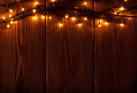 rustic christmas: Christmas lights on wooden background. View with copy space