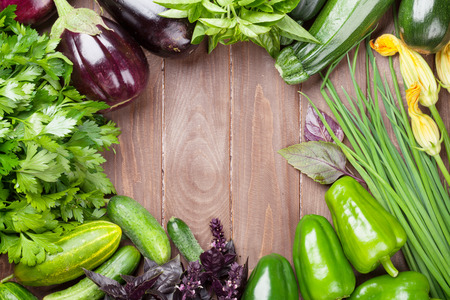 green vegetables: Fresh farmers garden vegetables and herbs on wooden table. Top view with copy space Stock Photo