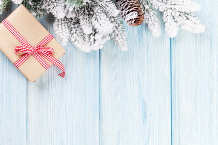 christmas backgrounds: Christmas wooden background with snow fir tree and gift box. View with copy space