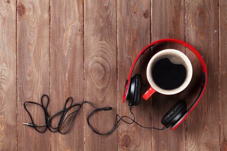 Headphones and coffee cup on wooden desk table. Music concept. Top view with copy space Stock Photo