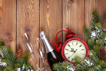 twelve month old: Christmas wooden background with clock, snow fir tree and champagne
